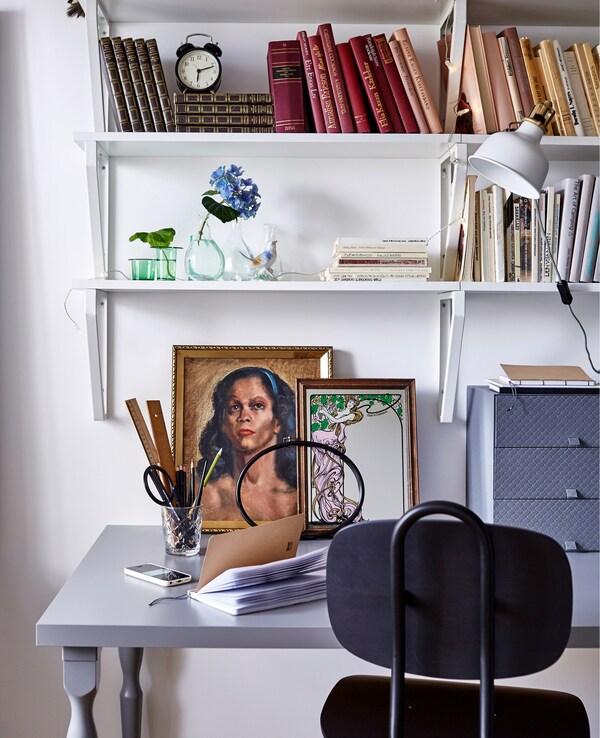 Un espacio de trabajo en un dormitorio blanco, que incluye una silla negra de oficina, un escritorio gris, dibujos y estanterías de pared con libros.