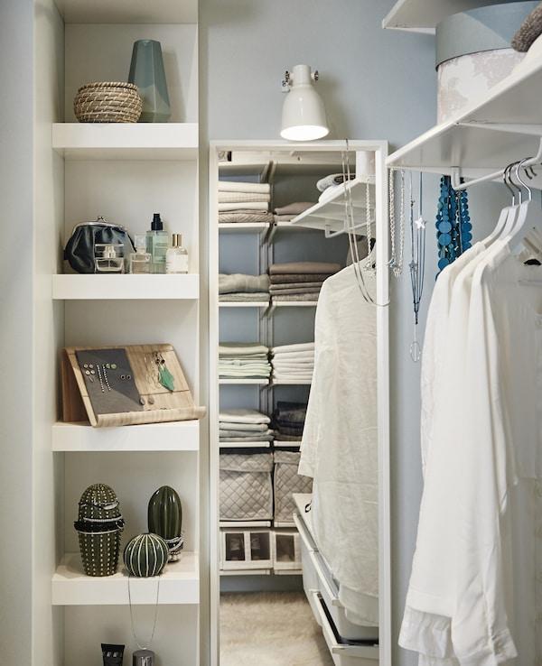 Un espacio para el tocador dentro del vestidor con una estantería para maquillaje y joyas, junto con un espejo de cuerpo entero.