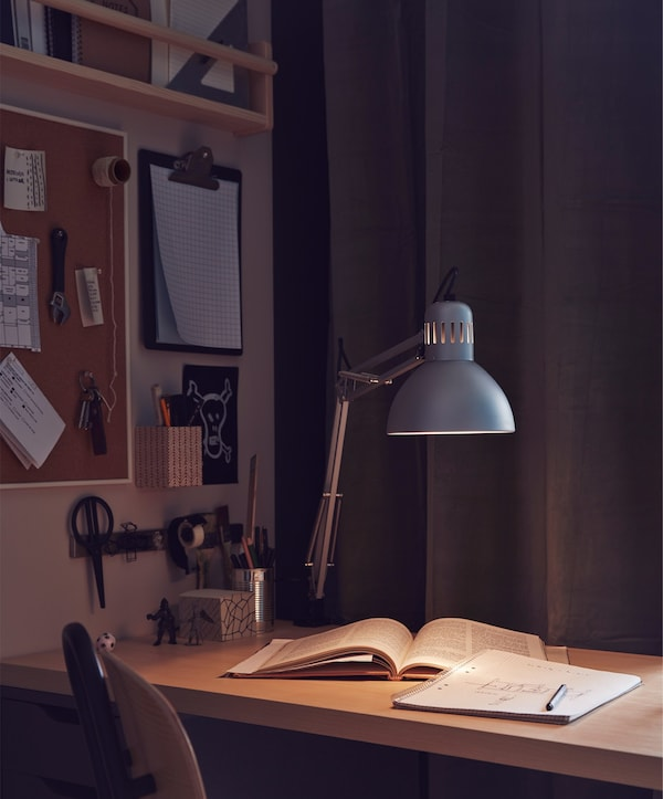 Un espai de treball lleugerament il·luminat amb un llum i llibres a l'escriptori.
