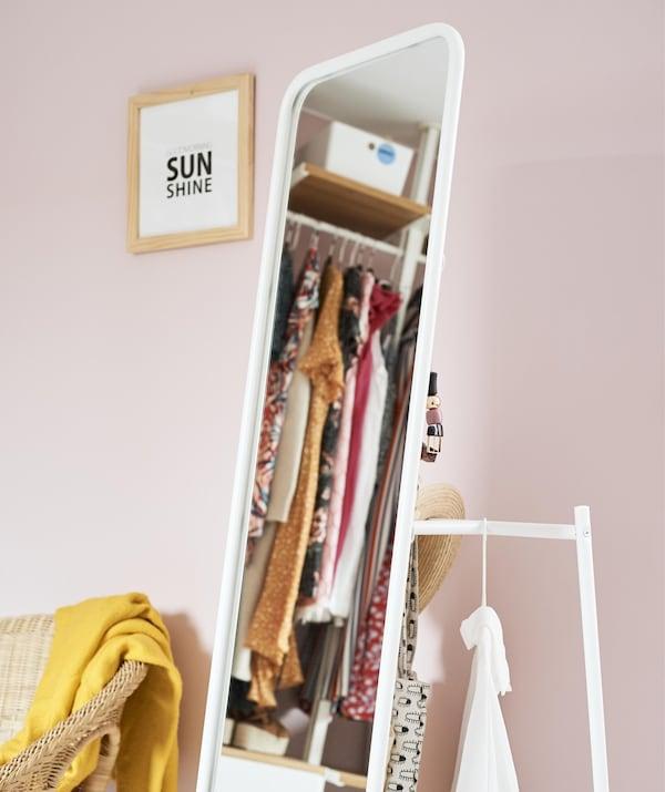 Un espejo de cuerpo entero con riel colgante detrás, junto a una pared de color rosa pálido.