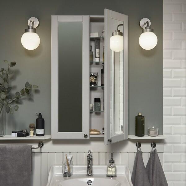 Un espello alto e pouco profundo sobre un lavabo branco. Unha porta aberta, que deixa ver artigos de coidado persoal dentro.