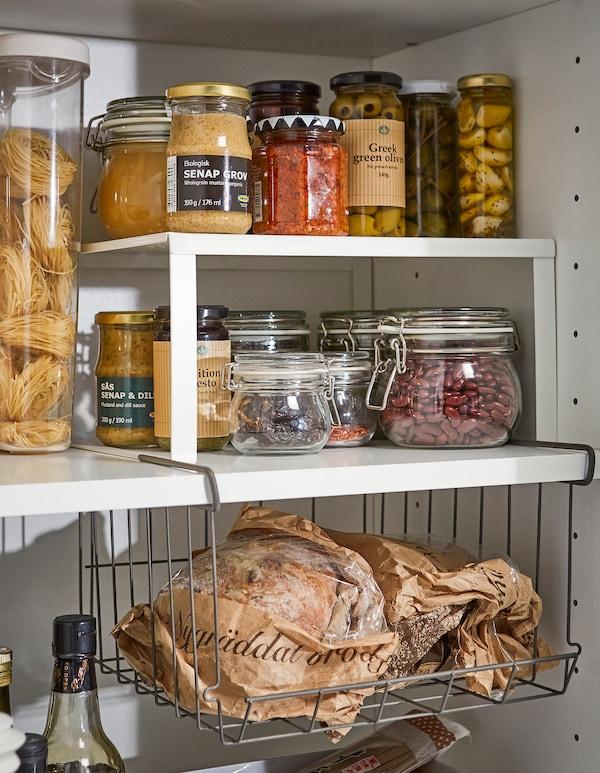 Un estante adicional IKEA VARIERA blanco y una cesta colgante OBSERVATÖR para crear espacio para almacenar mermeladas, tarros y botellas.
