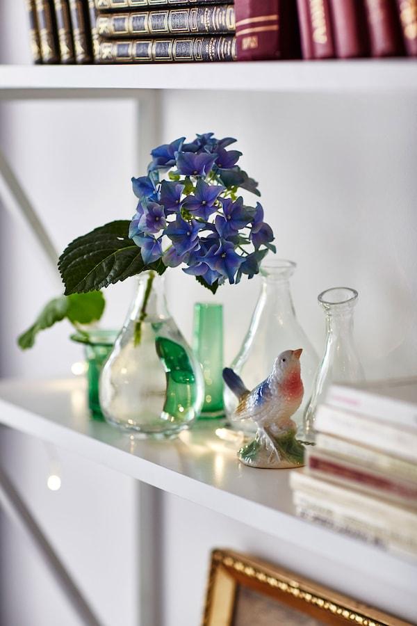 Un estante blanco está decorado con pequeños jarrones de cristal y una figurita de un pájaro.