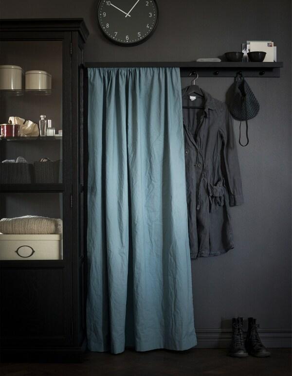 Un estante para cuadros es un estante para abrigos creativo, al que se han fijado pomos y tela por delante para ocultar el desorden.