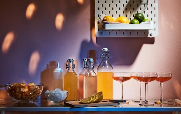Un étalage de boissons, de verres et d'accessoires sur une table d'appoint. Sur le mur au-dessus, des citrons jaunes et verts rangés dans un panneau perforé SKÅDIS.