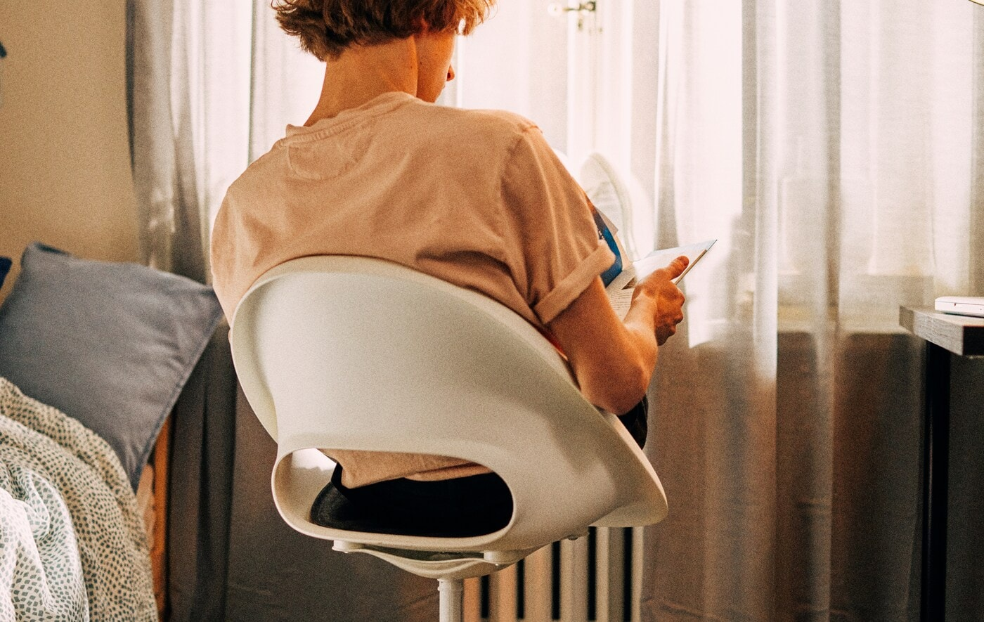 Un étudiant est assis dans une chaise pivotante face à la fenêtre, ses pieds reposant sur le radiateur devant lui pendant qu'il étudie.