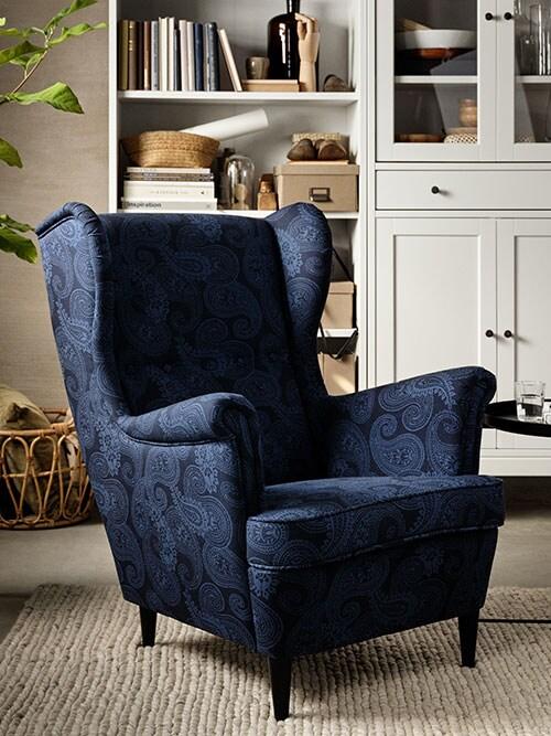 Un fauteuil à oreilles bleu foncé, une bibliothèque blanche, des livres, des boîtes avec couvercles beige foncé, des objets décoratifs.