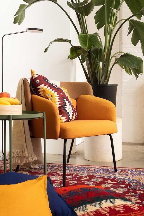 Un fauteuil BINGSTA jaune et une lampe sur pied noire à côté d'une grande plante vert verte sur un tapis oriental coloré recouvert de coussins.
