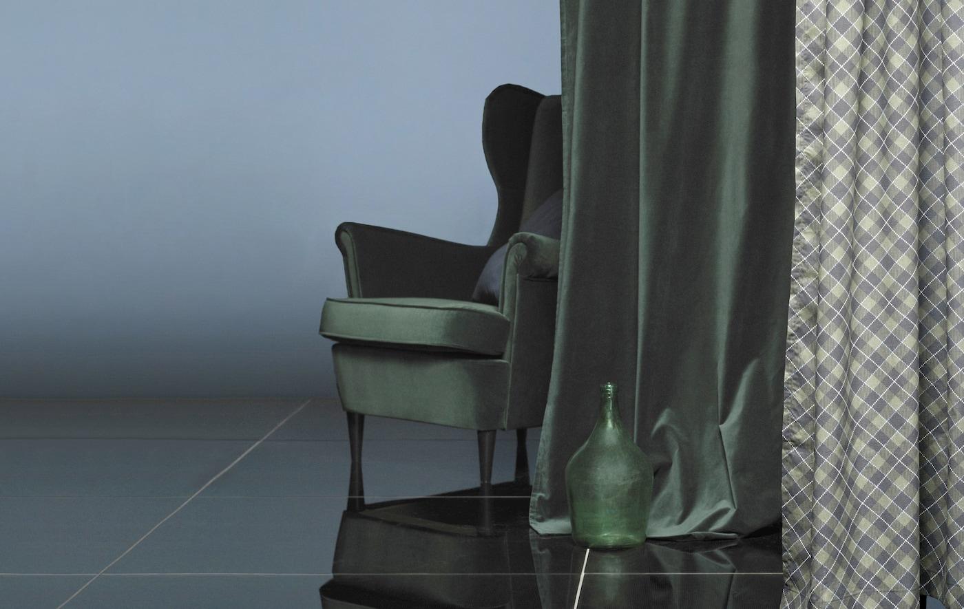 Un fauteuil derrière un rideau en velours vert foncé.