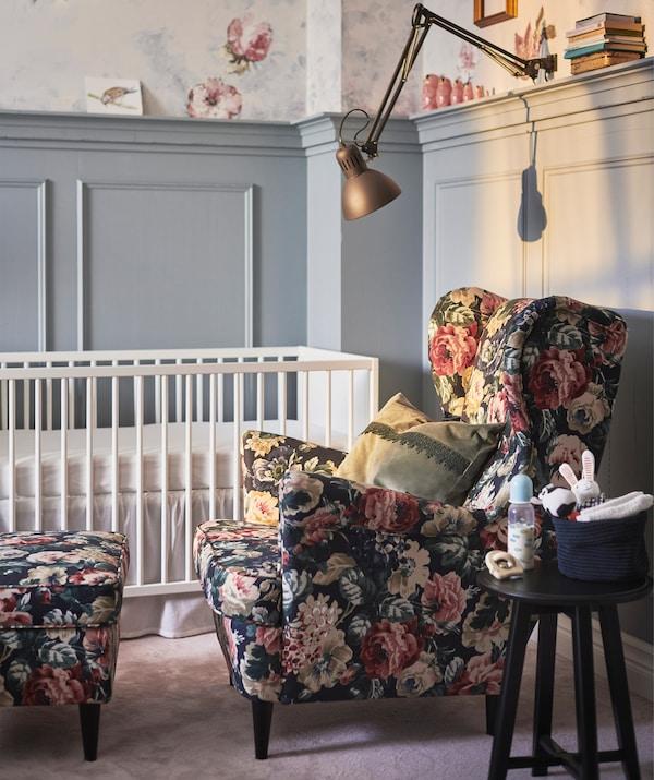 Un fauteuil fleuri et un repose-pieds à côté d'un berceau pour bébé au-dessus duquel se trouve un spot à pince.