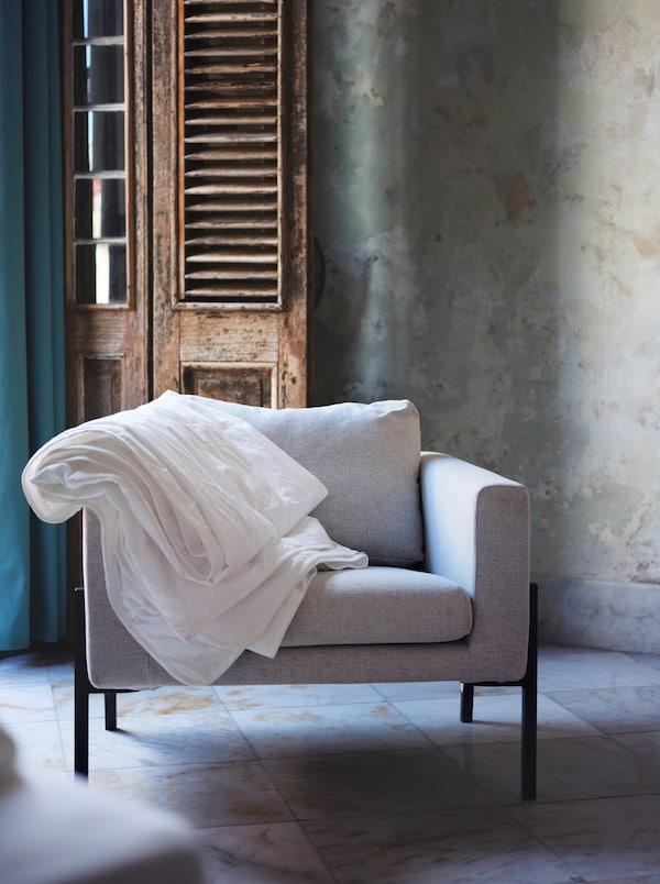 Un fauteuil gris dont l'accoudoir est recouvert d'une couette blanche, installé devant une porte rustique en bois sur une surface carrelée.