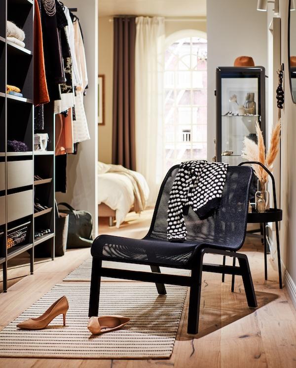 Un fauteuil noir près d'une garde-robe avec une paire d'escarpins au sol et un cardigan noir/blanc sur le dossier.