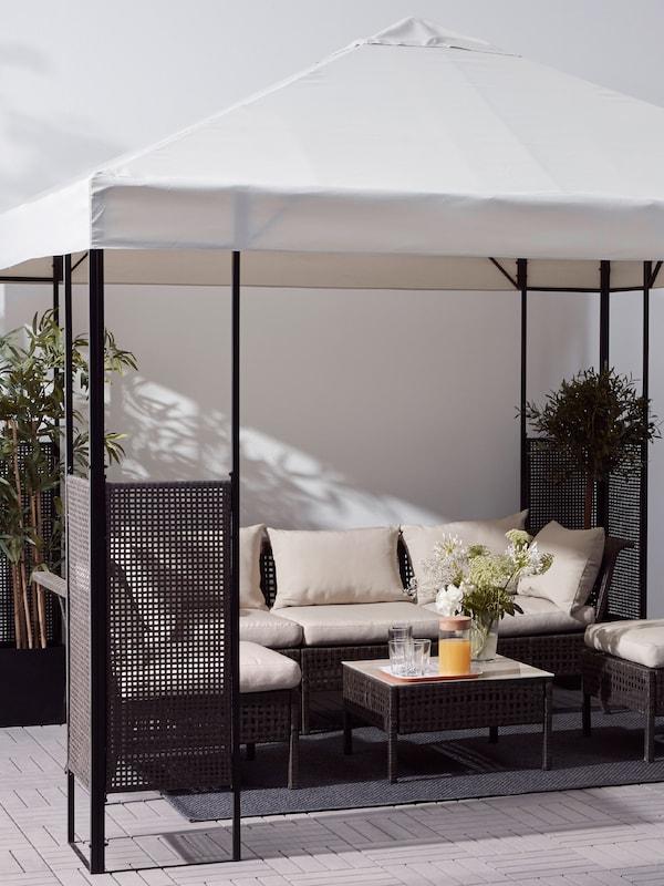 Un foișor cu acoperiș alb și cadru maro închis, o canapea de exterior și scaune cu perne și o masă cu plante.