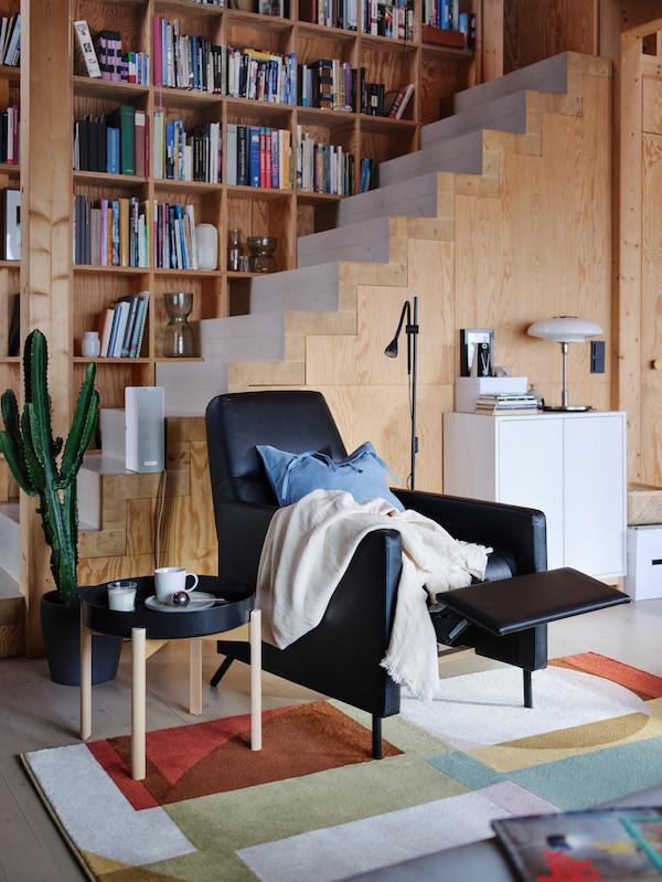 Un fotoliu rabatabil GISTAD negru acoperit cu pături se află într-o cameră cu pereți de lemn, cu sprijinul pentru picioare în poziție ridicată.