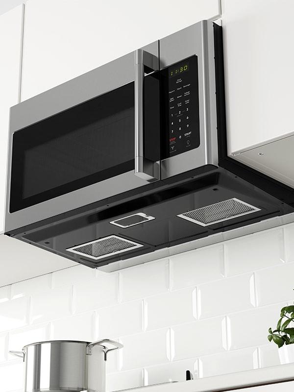 Un four à micro-ondes à hotte intégré MEDELNIVÅ en acier inoxydable noir.