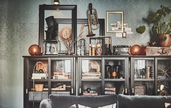 Un gabinete con puerta de vidrio IKEA MALSJÖ repleto de recuerdos, jarrones, libros, marcos y cajas.