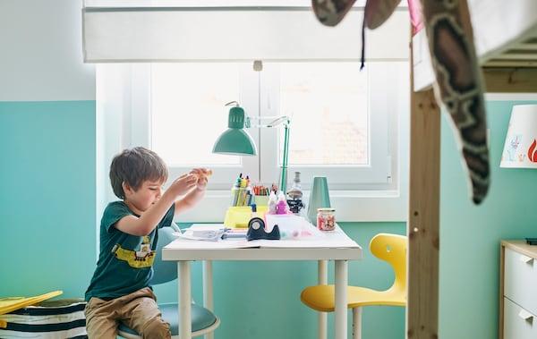 Un garçon assis sur une chaise blanche et turquoise à un bureau blanc, avec des stylos de couleur, une lampe de bureau verte et une chaise jaune en face.