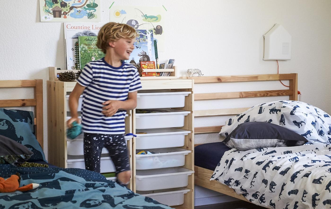 Un garçon dans une chambre d'enfant avec deux lits côte à côte, des rangements en bois et des textiles à motifs.