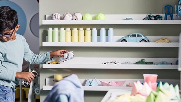 Un garçon range des balles, des bouteilles, des jouets, des objets en papier et de petites voitures sur quatre tablettes pour photos MOSSLANDA blanches accrochées au mur.