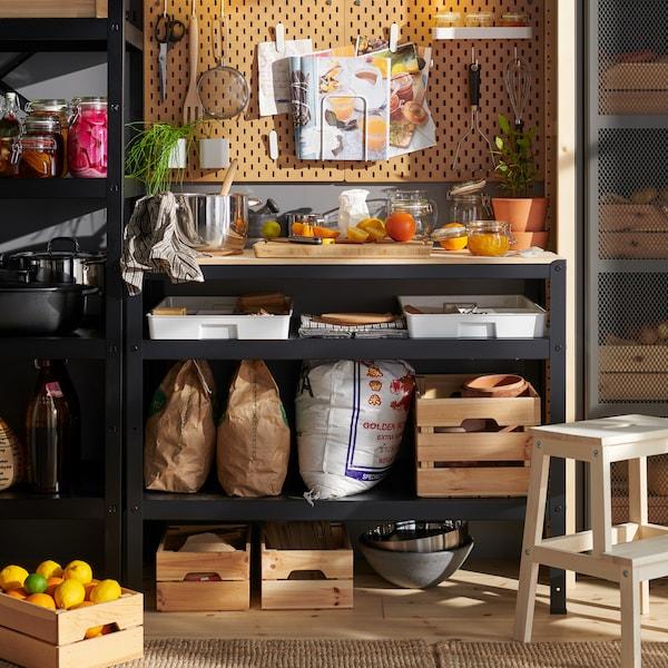 Un garde-manger comprenant un mur entièrement recouvert d'étagères, d'éléments et de boîtes dédiés au rangement de divers aliments et articles de cuisine.