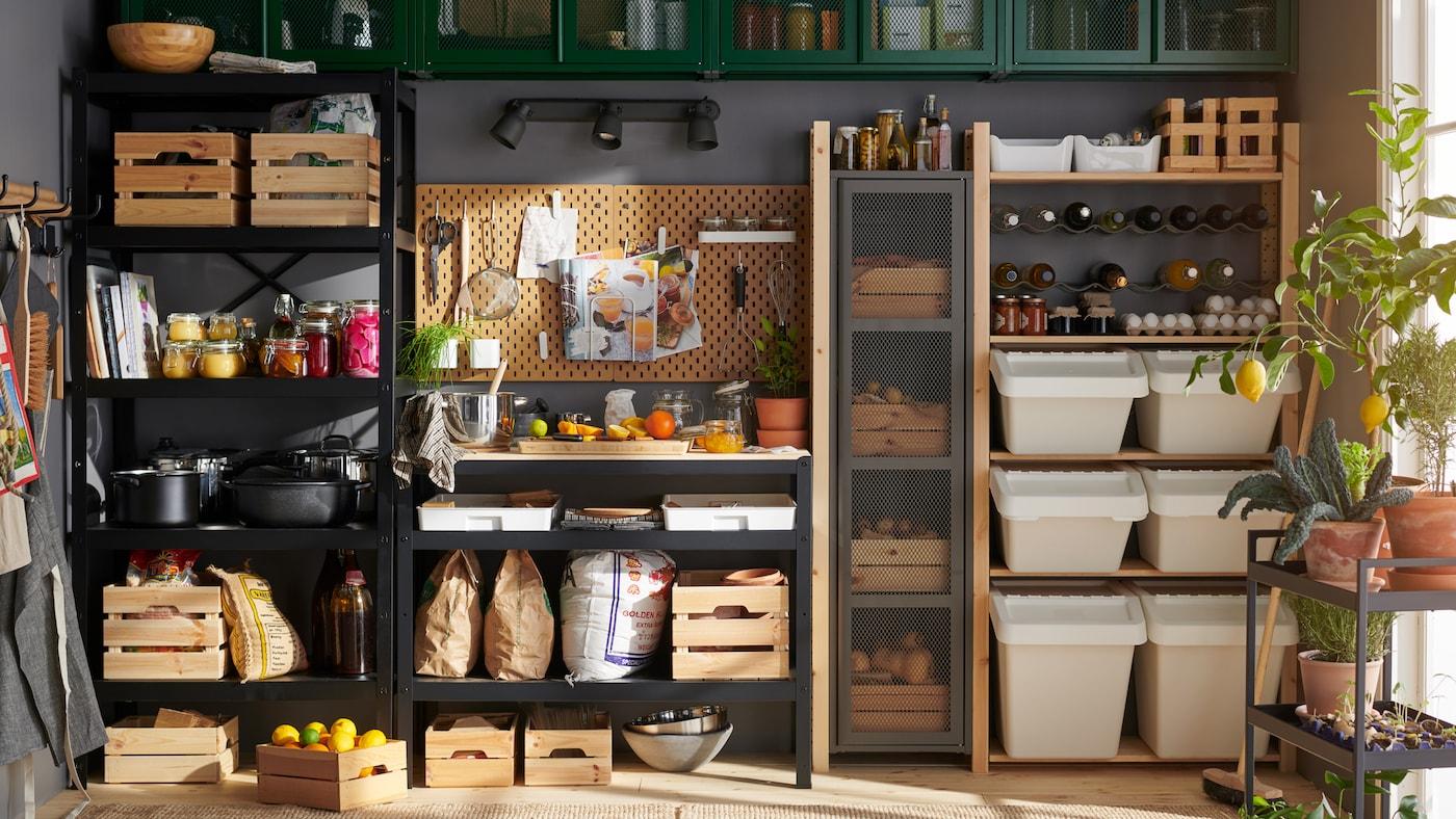 Un garde-manger comprenant un mur entièrement recouvert d'étagères, d'armoires et de boîtes dédiées au rangement de divers aliments et articles de cuisine.