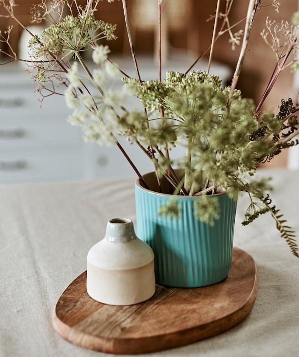 Un ghiveci turcoaz folosit ca vază pentru un buchet de frunze sălbatice și un vas mic din ceramică expuse pe un tocător.