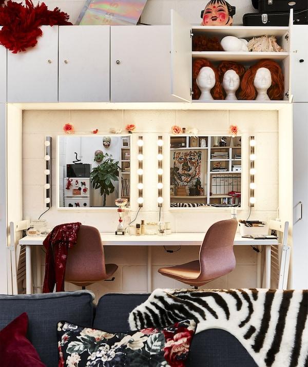 Un gran toucador con dúas cadeiras rosas e dous espellos con luces arredor dos bordos.
