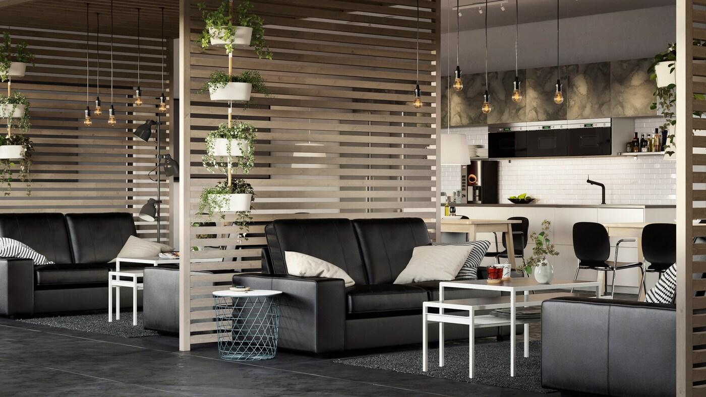 Un grand bureau professionnel aéré avec des canapés en cuir noir KIVIK et des cloisons en lattes de bois.