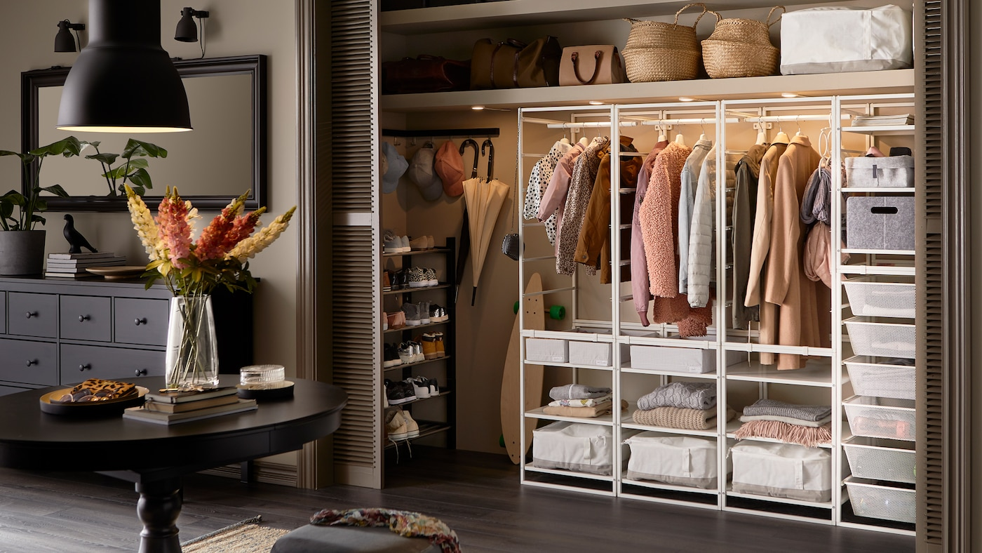 Un grand couloir où se trouve une armoire-penderie encastrable avec un agencement JONAXEL, des vêtements, des boîtes de rangement et des paniers à l'intérieur.