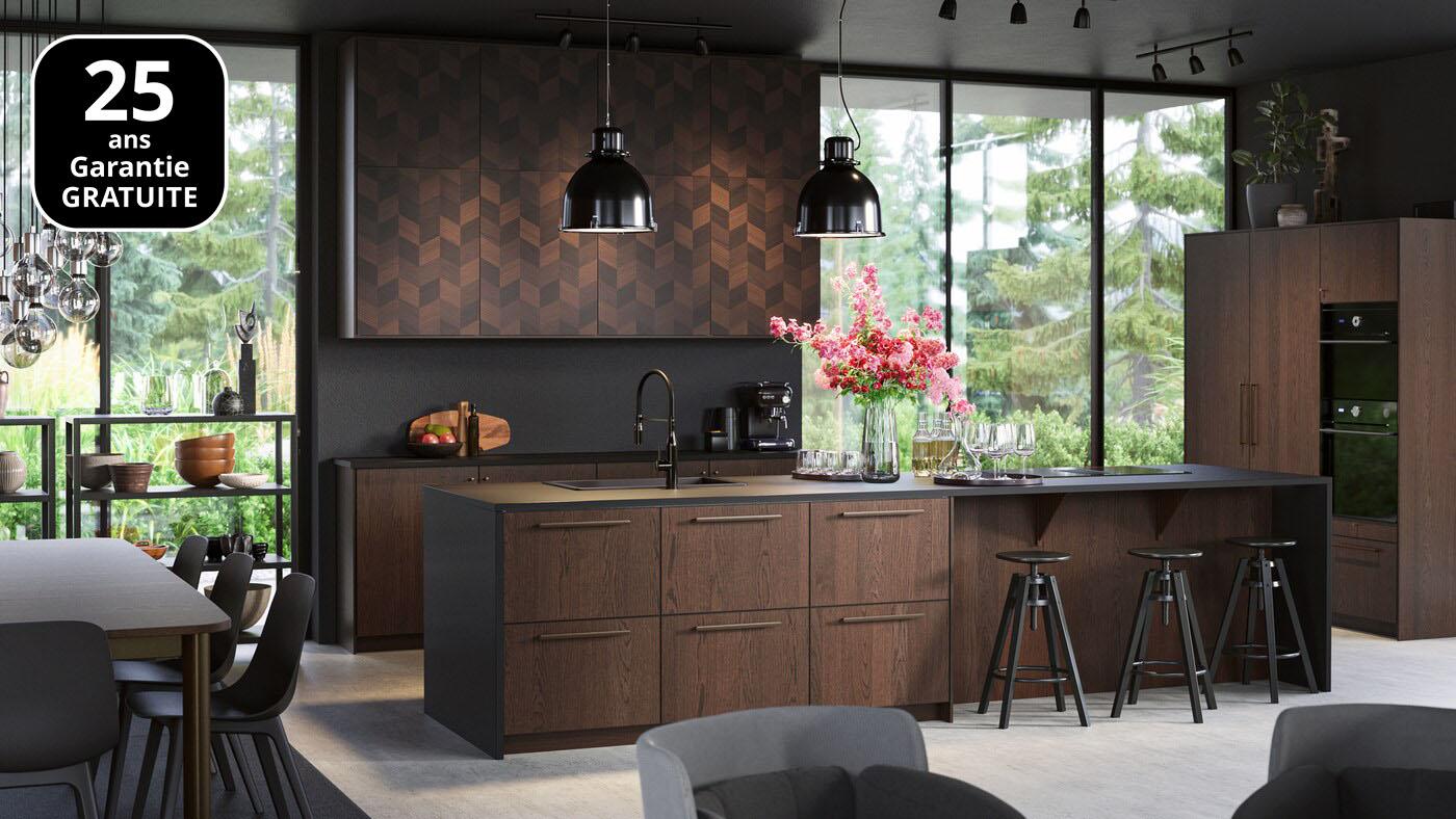 Un grand îlot de cuisine élégant avec des façades en bois. Des tabourets de bar noirs, des suspensions noires, un réfrigérateur avec des portes en bois.