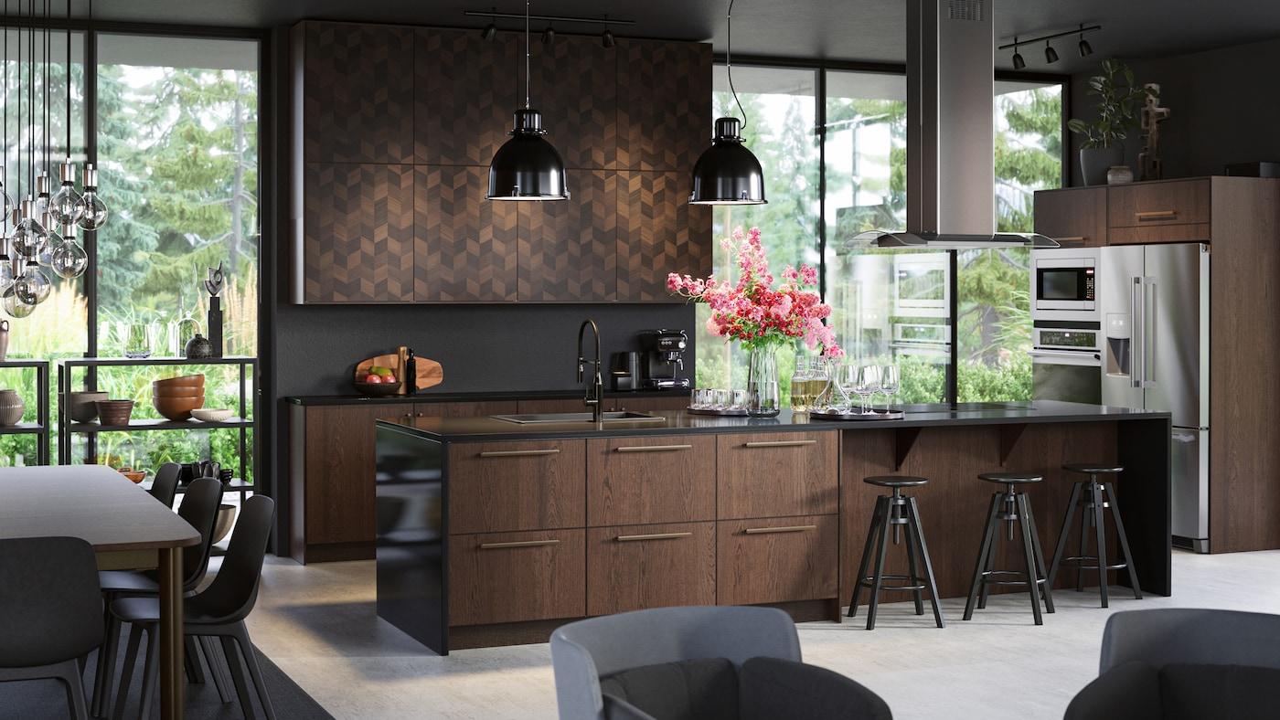 Un grand îlot de cuisine élégant doté de façades en bois, des tabourets de bar noirs, des suspensions noires et une hotte aspirante de plafond.
