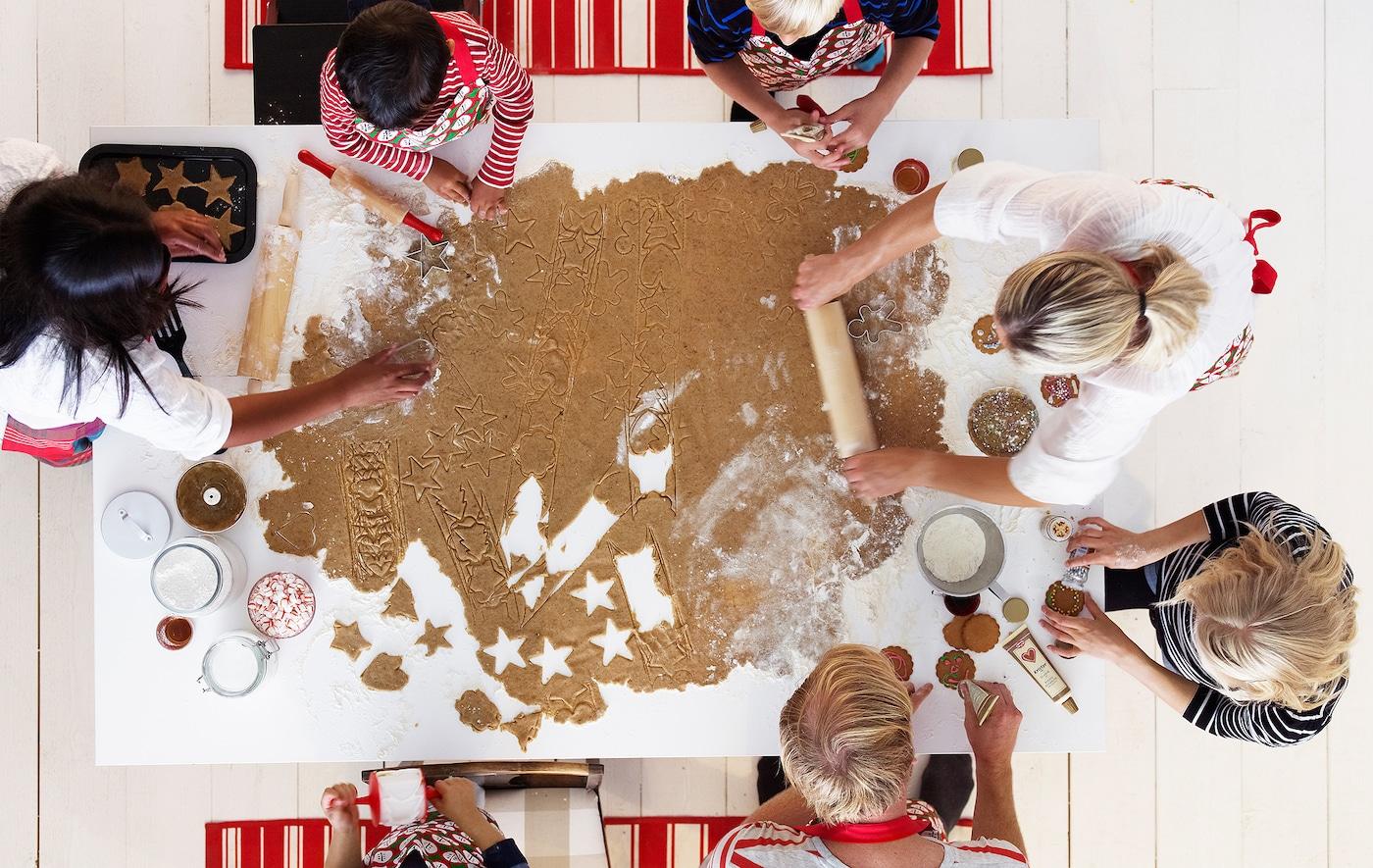 Un groupe d'adultes et d'enfants occupés à travailler une très grande pâte de biscuit à pain d'épice étalée sur une table de cuisine.