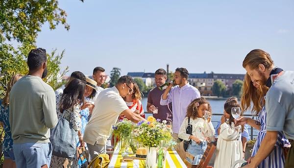 Un groupe de personnes en train de préparer une longue table pour l'extérieur en une belle journée d'été.