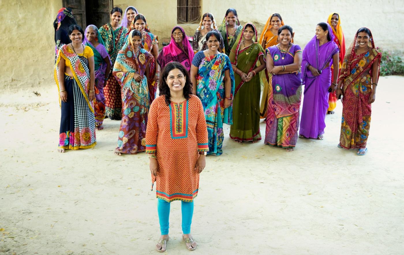 Un groupe d'environ quinze femmes souriantes dans des robes longues colorées debout dans une rue non pavée.