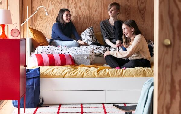 Un grup d'amics adolescents parlen mentre seuen junts en un llit extensible SLÄKT en un dormitori amb les parets folrades amb plafons de fusta.