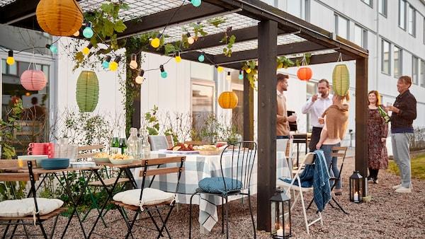 Un grupo de personas de pie junto a una fila de sillas y mesas pequeñas disfrutando de una fiesta bajo una pérgola decorada en un patio.