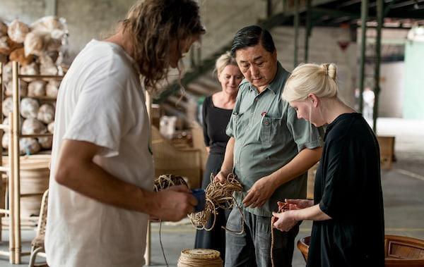 Un grupo de personas que manejan cuerdas y materiales en un almacén con muebles de ratán.