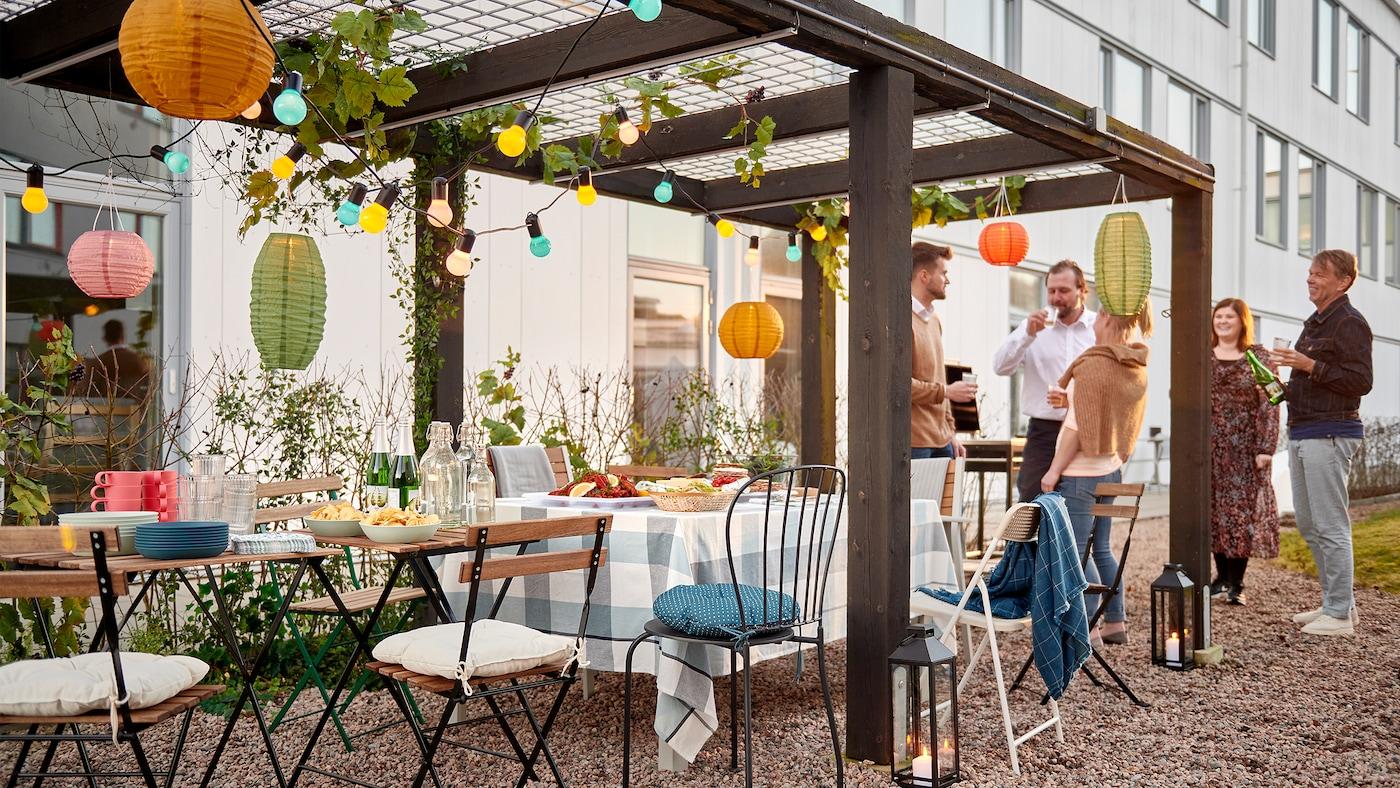 Un gruppo di persone in piedi, vicino a una fila di sedie e a dei piccoli tavoli apparecchiati per una festa sotto una pergola decorata in un cortile.