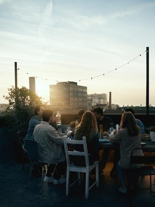 Un gruppo di persone sedute attorno a un tavolo al calar del sole mentre mangiano e bevono. Sullo sfondo, alcuni palazzi - IKEA