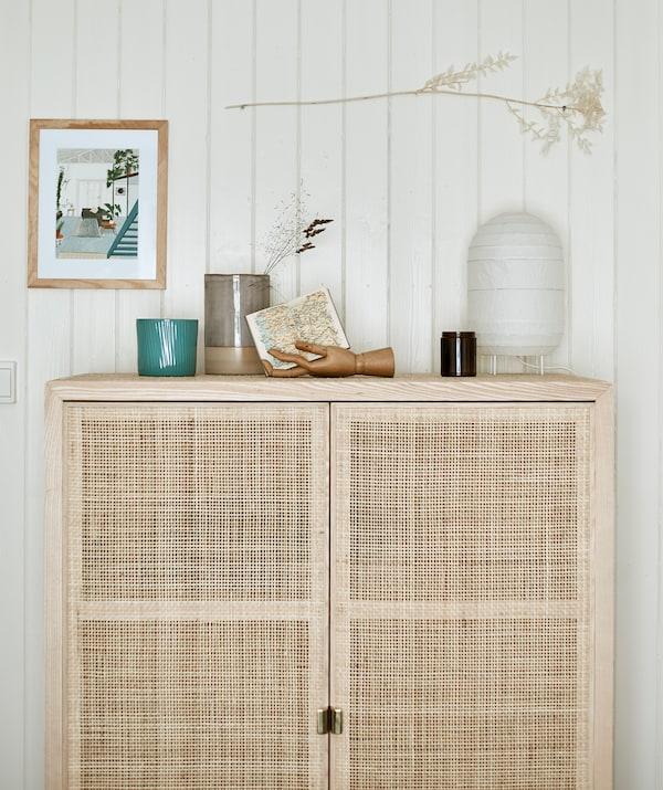 Un haut meuble de rangement en bois à portes tissées debout devant un mur à lambris, surmonté d'une lanterne de papier et d'autres objets.