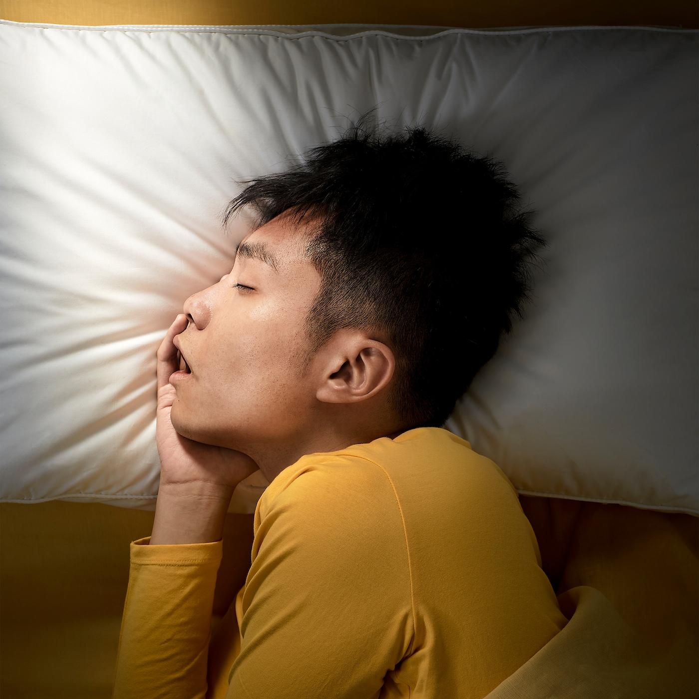 Un hombre joven duerme plácidamente de lado con una almohada ergonómica IKEA PRAKTVÄDD.