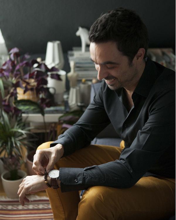 Un hombre sentado en una habitación con una planta.