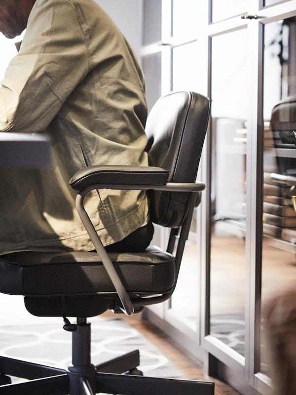 Un hombre sentado en una silla de oficina ALEFJÄLL frente a varios libreros BILLY.