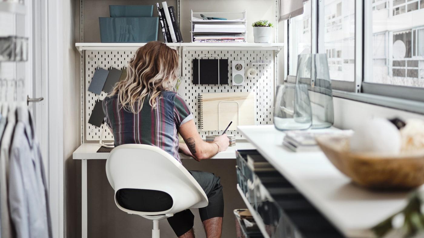 Un homme assis sur une chaise pivotante beige/blanche devant un bureau blanc surmonté d'un système de rangement blanc, sur un balcon fermé.