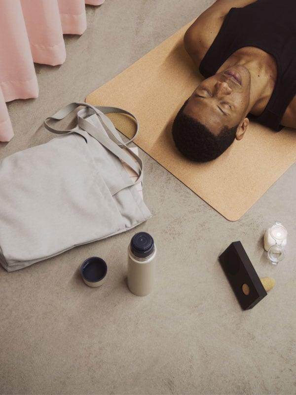 Un homme couché sur le dos qui écoute de la musique sur un tapis de yoga jaune pâle
