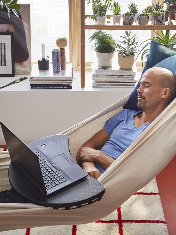 Un homme couché sur un hamac avec un support pour ordinateur portatif sur ses genoux