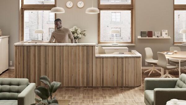 Un homme debout à un comptoir d'accueil en bois clair devant deux fenêtres. Deux suspensions sont au plafond et des horloges sont fixées au mur.
