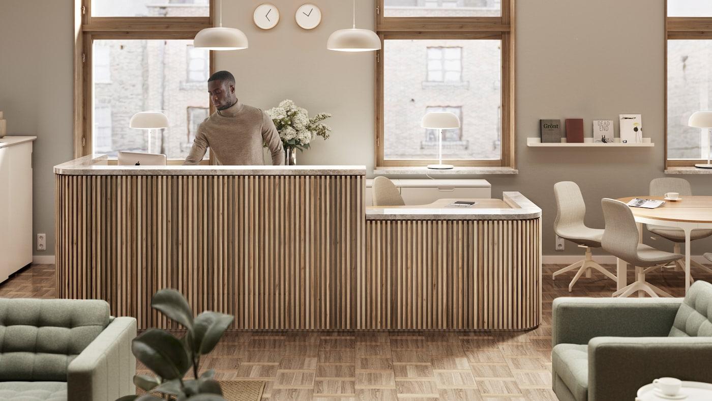 Un homme debout derrière un comptoir de réception devant deux fenêtres. Deux suspensions pendent du plafond et le mur est orné de quatre horloges.