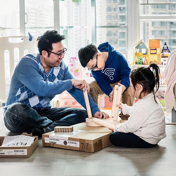 Un homme et 2 enfants assis par terre en train d'assembler un tabouret