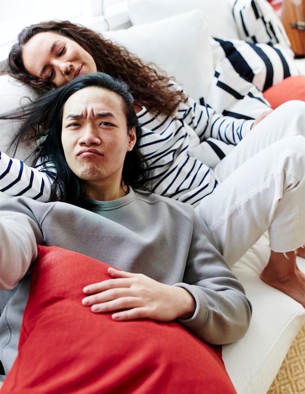 Un homme et une femme blottis ensemble sur un canapé blanc, entourés de coussins noirs et blancs rayés et colorés.